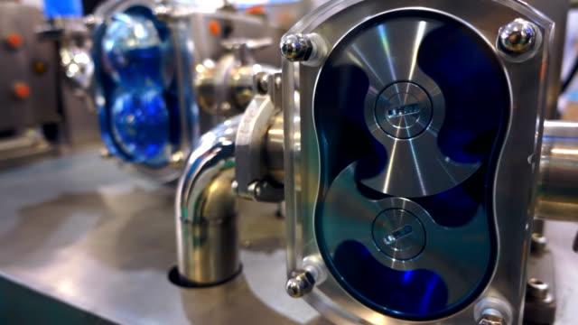 Shiny chrome motors pumping blue fluid through the pipeline video