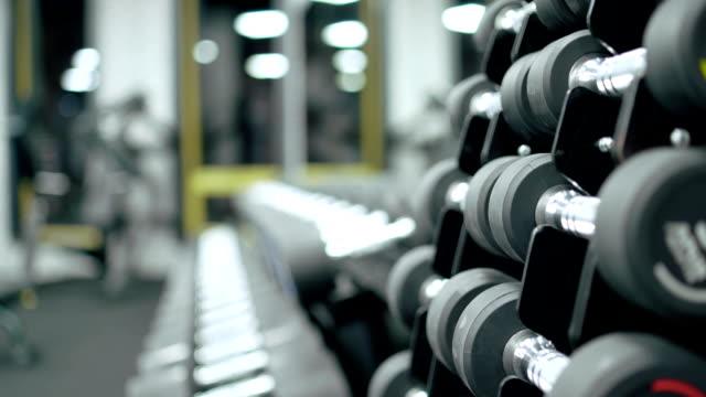 체육관에서 스탠드에 빛나는 금속 아령. - 운동장비 스톡 비디오 및 b-롤 화면