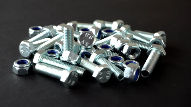 shiny nuts and bolts rotating on a black background. seamless loop. prores fullhd - затягивание стоковые видео и кадры b-roll