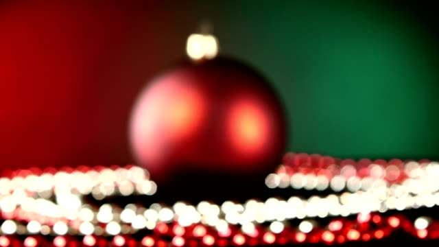 Shiny red toy for Christmas or New Year and beads, rotation, on green, bokeh, dynamic change of focus video