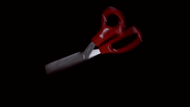 Shiny scissors with red, white handles flies and rotates on a black background video