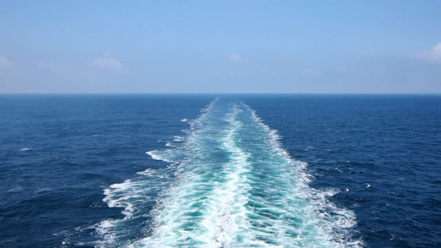 Ship wake on the ocean. Water foam trace behind the large ship goes till the horizon. video