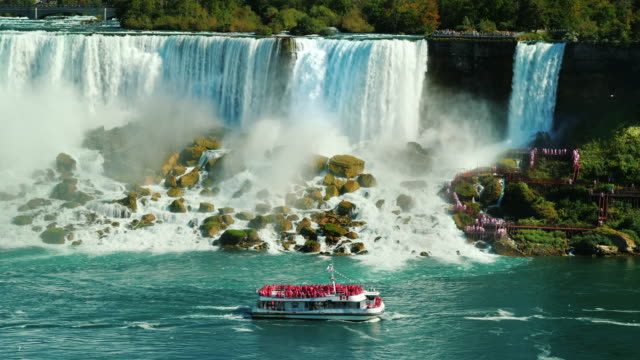 A ship with tourists sails under the famous Niagara Falls. View from the Canadian coast