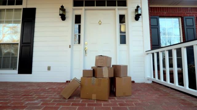 scatole di spedizione sul portico anteriore - portico video stock e b–roll