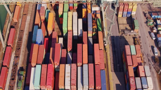 Shipping Containers Beneath Straddle Carrier - Drone Shot With Upwards Tilt video