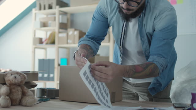 Shipping Online Orders Bearded man packing packages and adding bar code. post office stock videos & royalty-free footage