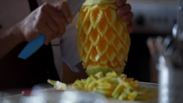 Ship's chef cutting a pineapple into a work of art