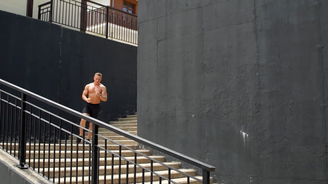 vídeos de stock e filmes b-roll de shirtless handsome male runner on steps of stairs over urban background - tronco nu