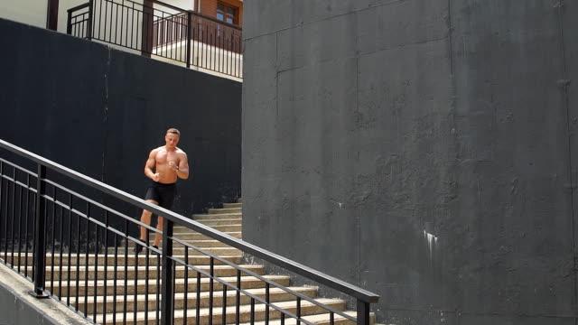 shirtless stattlich männlichen läufer auf treppenstufen über städtischen hintergrund - nackter oberkörper stock-videos und b-roll-filmmaterial