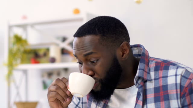 Shocked african american man burn tongue with hot drink, actively breathing