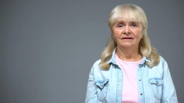 vídeos y material grabado en eventos de stock de mujer de envejecimiento dado una sacudida eléctrica que cubre la boca con la mano, sorprendido con la noticia, las emociones - geriatría