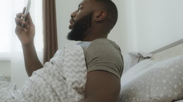 ベッドに座っているショックを受けた黒人男性。スマートフォンが人の手から落ちる。 - スマホ ベッド点の映像素材/bロール