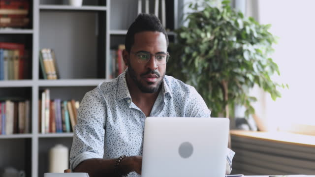 Shocked frustrated african man feel stressed look at computer