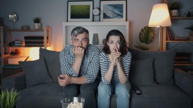 zszokowana dziewczyna i facet oglądający telewizję z poważnymi twarzami dotykającymi twarzy w nocy - żona filmów i materiałów b-roll