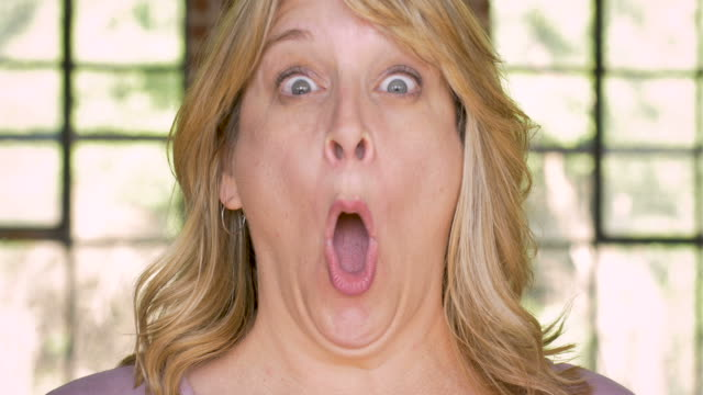 shocked woman expressing her surprise with her mouth open - sorpresa video stock e b–roll