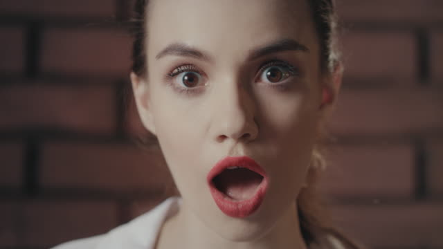 Shocked woman with opened mouth and eyes front camera on brick wall background. Shocked woman face with opened mouth and eyes looking to camera on brick wall background. Portrait amazed girl with red lips and opened mouth in surprise. Facial people emotion mouth open stock videos & royalty-free footage
