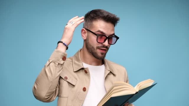 shocked young casual man reading book, covering mouth with hand while reading, pointing finger to the book and gesturing, throwing away the book and smiling on blue background