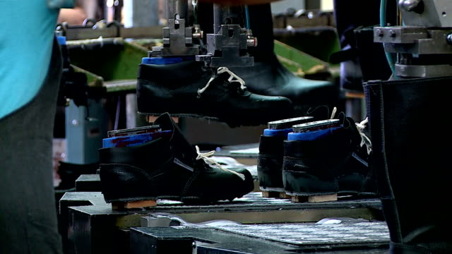 shoe factory conveyor sewing work and children's shoes cutting machines and casting soles - scarpe video stock e b–roll