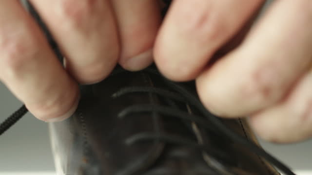 Shoe Lacing Hands doing up the laces on a shiny black dress shoe.  Shot with a macro lens and shallow depth of field. dress shoe stock videos & royalty-free footage
