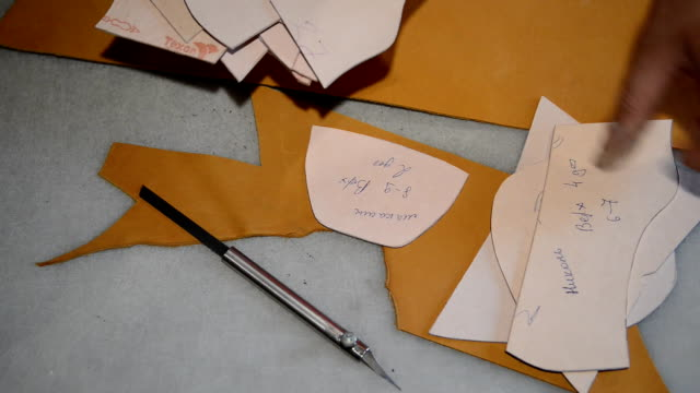 Shoemaker makes pattern on paper and cuts leather video