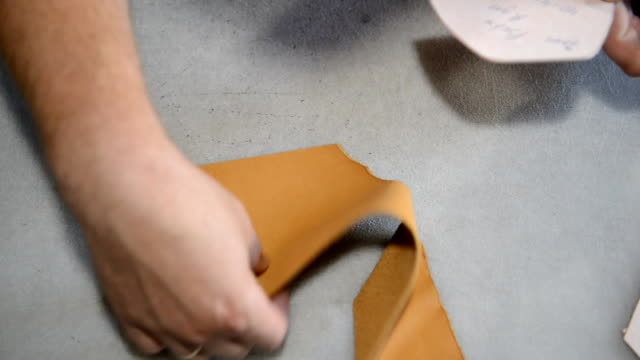shoemaker makes pattern on paper and cuts leather - cucitura video stock e b–roll