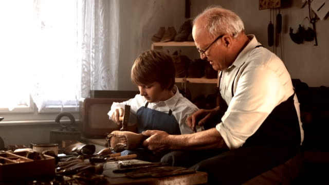 hd dolly: shoemaker teaching young apprentice - grandparents stock videos & royalty-free footage