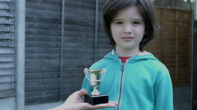 Shoot of a cute child posing and smiling at camera with his trophy video