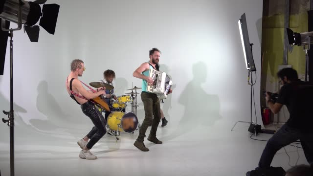 Shooting a clip of a punk rock band. A videographer is working. The musicians are jumping with instruments. The bass player is dressed in a women's dress and wig. The frame has an accordion, balalaika and drummer.