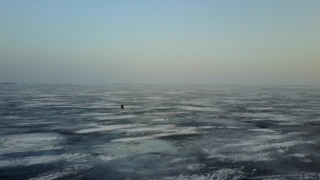 schießen drone winterlandschaft am fluss. die leute fahren auf einem schneemobil. norden - schneeflocke sonnenaufgang stock-videos und b-roll-filmmaterial