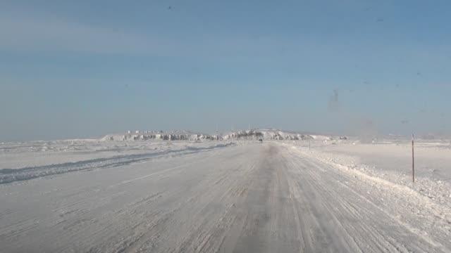 vídeos y material grabado en eventos de stock de disparando desde la carretera del coche en la ciudad de anadyr en el lejano norte. - nieve amontonada