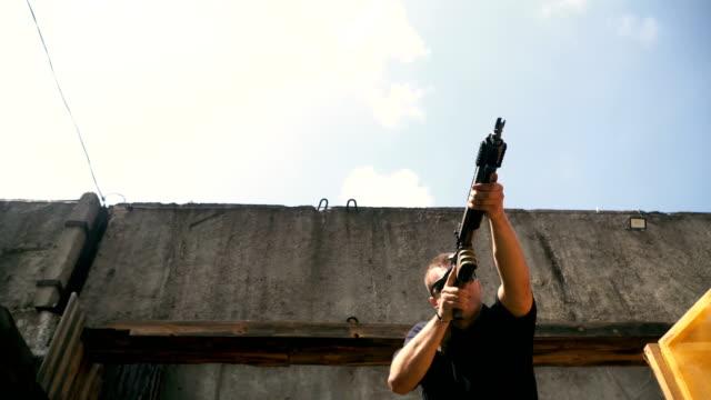 dreharbeiten in einem strich. der mann schießt in einen strich mit einem halbautomatischen gewehr - zielscheibe stock-videos und b-roll-filmmaterial