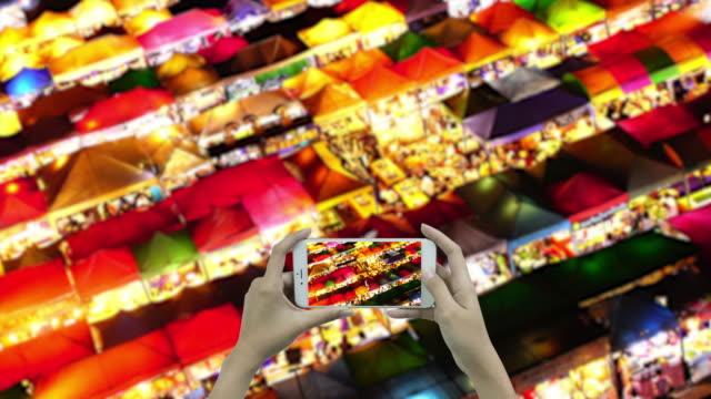 nachtmarkt mit handy schießen - trefferversuch stock-videos und b-roll-filmmaterial