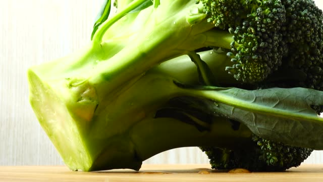 Shooting of broccoli in the movement. Cuttig board.