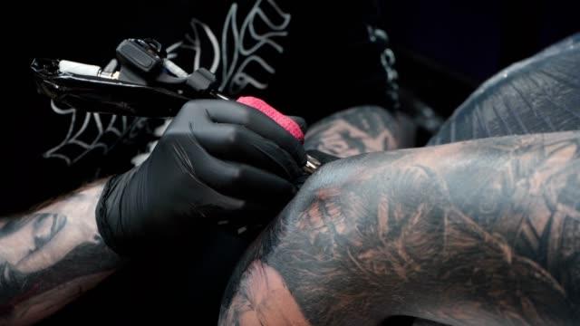 schießen von mann immer tattoo auf arm im salon - menschliches gelenk stock-videos und b-roll-filmmaterial