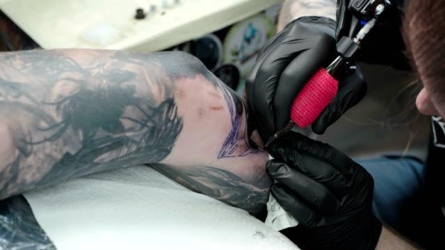 schießen von mann machen tattoo auf ellenbogen in salon - menschliches gelenk stock-videos und b-roll-filmmaterial