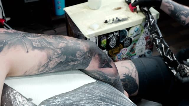 schießen von tätowierer immer tattoo auf ellenbogen im salon - menschliches gelenk stock-videos und b-roll-filmmaterial