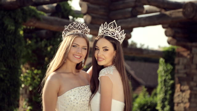 shooting of two gorgeous girls in wedding dresses and crowns with precious stones for the fashion magazine outdoors in the park - prom fashion stock videos and b-roll footage