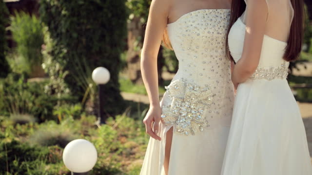 shooting of two lovely girls in wedding dresses and tiaras for a fashion magazine outdoors in the park - prom fashion stock videos and b-roll footage