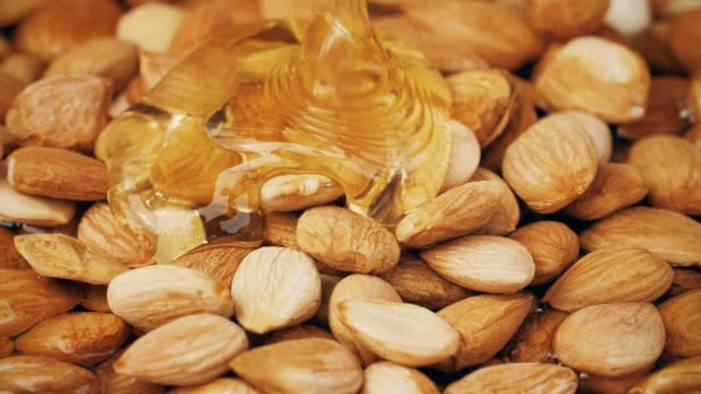 shooting pouring honey on almond with high speed camera. - miele dolci video stock e b–roll