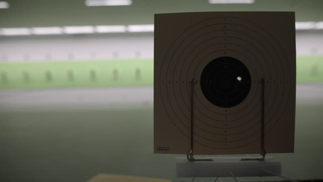 Shooting target with bullet hole at shooting range
