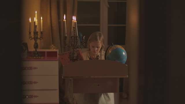 Shooting through doorway of Caucasian schoolgirl doing homework at home in candlelight. Blond child sitting at the desk with globe on it, and writing down. Education, generation Z.