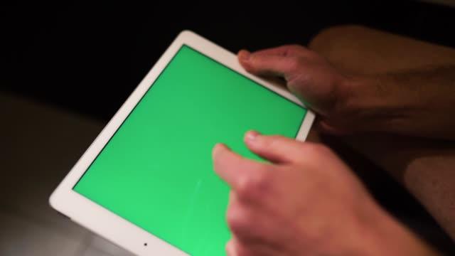 vidéos et rushes de vidéo de tir du processus où l'homme tient la tablette dans les mains et glisser vers la droite. écran vert. le type s'assoit dans les toilettes ou la salle de repos. - homme slip