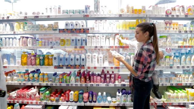 vídeos de stock, filmes e b-roll de assistente de loja, usando o leitor de código de barras para ajudar a mãe com criança para escolher o produto de higiene - prateleira objeto manufaturado