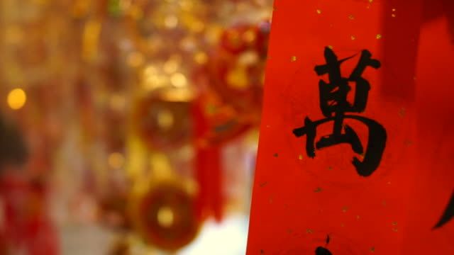 Shop hanging chinese new year decorations. Colorful red, gold and good words decorative pendants and paper around
