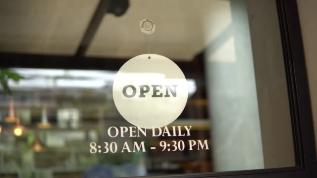 shop owner changing sign from closed to open and locking up - open sign stock videos & royalty-free footage