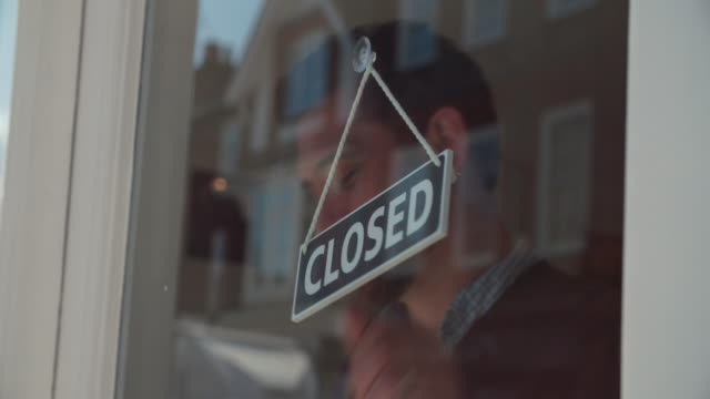 Shop owner changing sign from open to closed and locking up video