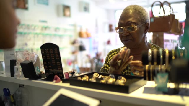 vídeos de stock, filmes e b-roll de proprietário de loja que ajuda o cliente que escolhe um anel - brasileiro pardo