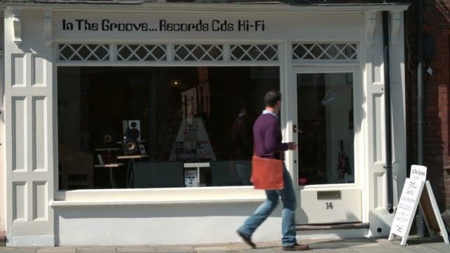 Shop owner opening up record, CD and hi-fi shop video