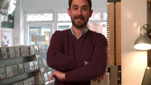 Shop owner posing in a record shop, smiling video
