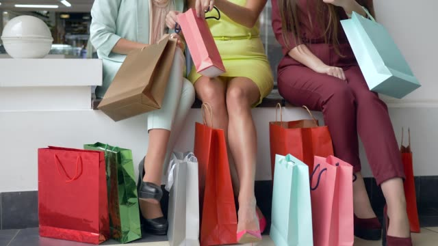 shopaholic girls are watching new purchases in season of discounts and sales and lot bright shopping bags near feet - borsa della spesa video stock e b–roll